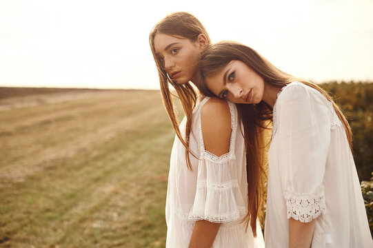 Two fair-haired girls in fashionable and stylish clothes among the fields on a background of sky.