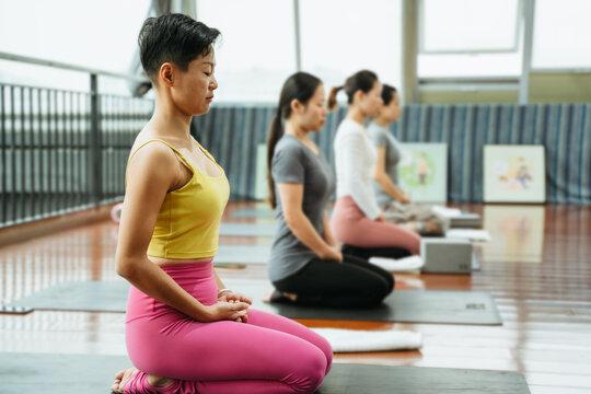 Young women practice yoga in a yoga studio