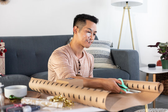 Man Smokes Joint and Cuts Wrapping Paper