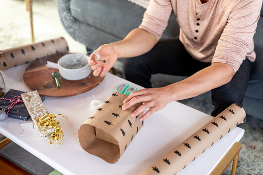 Man Holds Joint and Finishes Wrapping Gift
