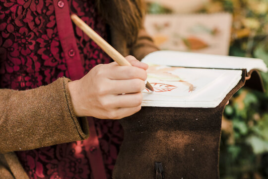 Closeup of a Young Woman Painting a Leaf