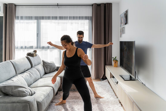 Young couple at home doing yoga in living room in front of TV watching online tutorial