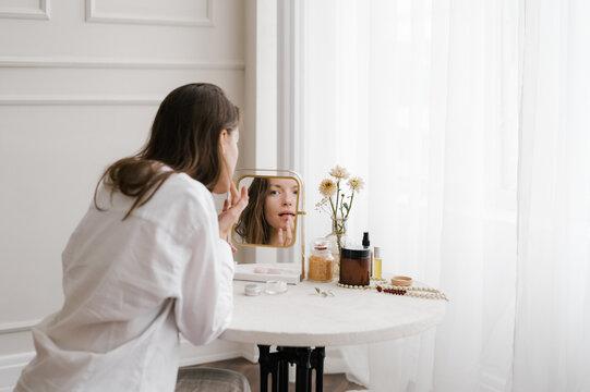 Anonymous woman applying lipstick on lips
