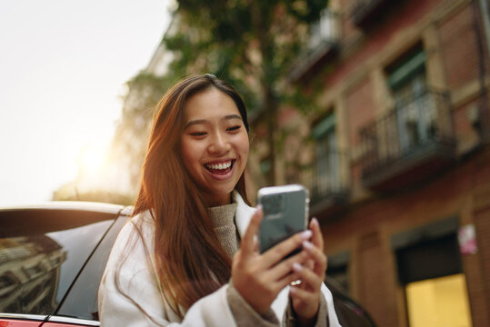 Asian woman laughing while using a mobile phone