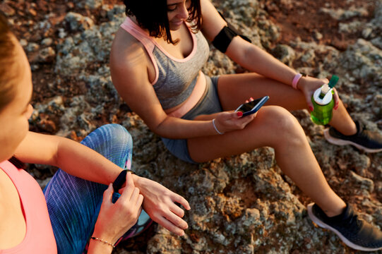 Smiling women checking their devices after a trail run
