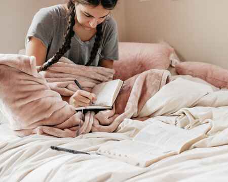 young woman journaling in her bedroom
