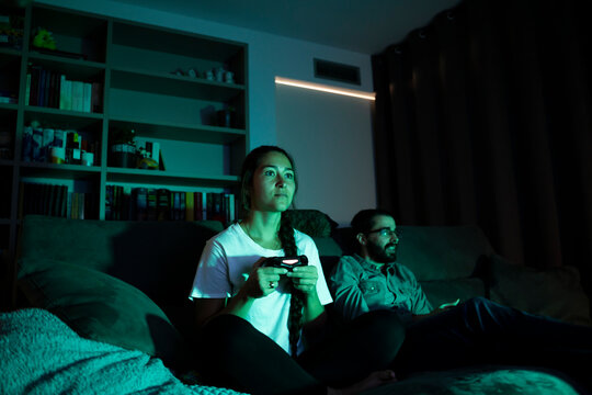 Young couple watching movie and playing video games in living room at night