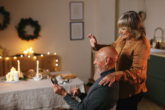 Cheerful senior couple communicating with friends via smartphone during Christmas holiday