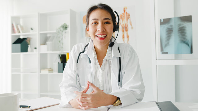 Young Asia lady doctor in white medical uniform with stethoscope using computer laptop talk video conference call with patient, looking at camera in health hospital. Consulting and therapy concept.