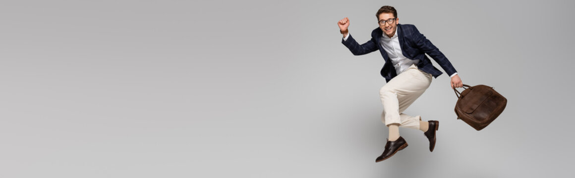 full length of cheerful businessman with leather bag levitating on grey, banner