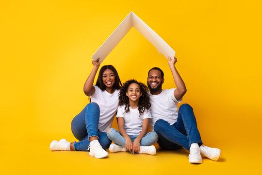 Black parents sitting under cardboard roof above daughter