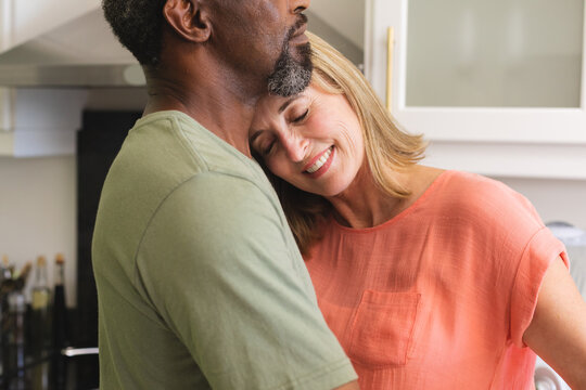 Diverse senior couple dancing in kitchen and embracing