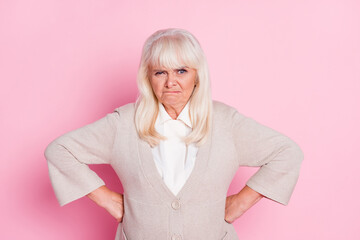 Photo of aggressive old woman annoyed face hands hips wear beige cardigan isolated pastel pink color background