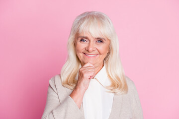 Photo portrait of thoughtful old woman touching face chin with finger isolated on pastel pink colored background