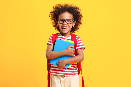 Happy schoolkid laughs at camera standing in studio with copybooks in hands