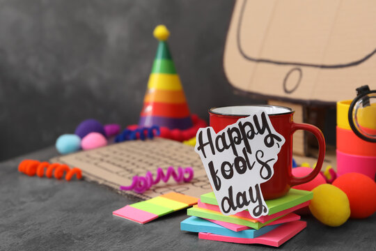 Cup with words Happy Fool's Day at fake workplace in office