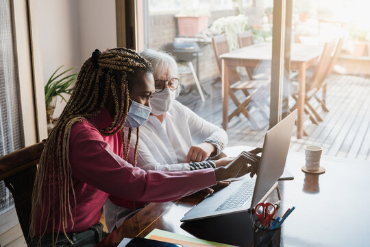 Multiracial young and senior business people with protective masks working inside modern office - Focus on african woman face