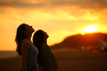 Two women silhouette breathing fresh air at sunset