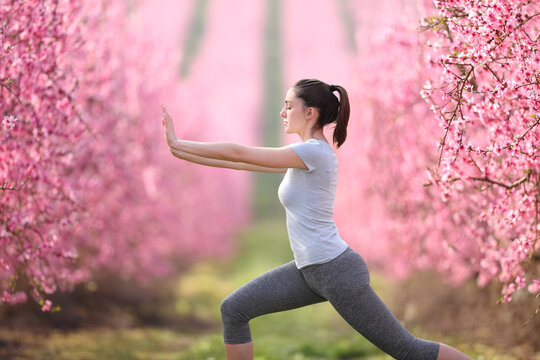 Woman doing tai chi exercise in a pink flowered field