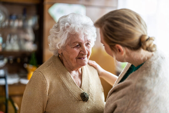 Health visitor talking to a senior woman during home visit