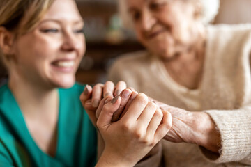 Cropped shot of a senior woman holding hands with a nurse