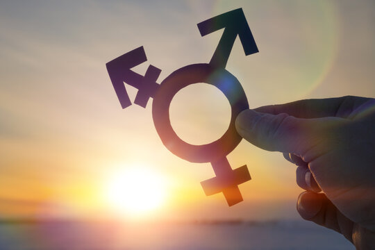 Transgender symbol in the hand of a man against the background of the sunset.