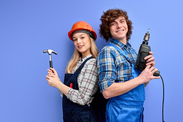 pleassant team of constructors builders stand back to back to each other holding tools Wall mural