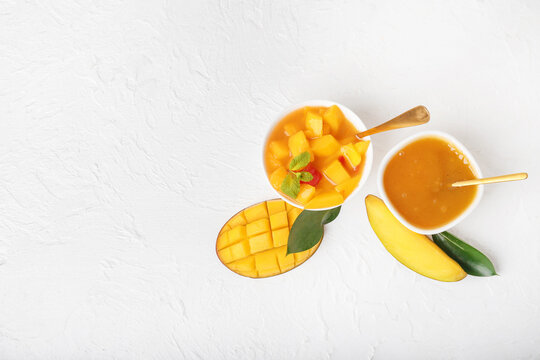 Bowls with mango sauce and fruit salad on light background