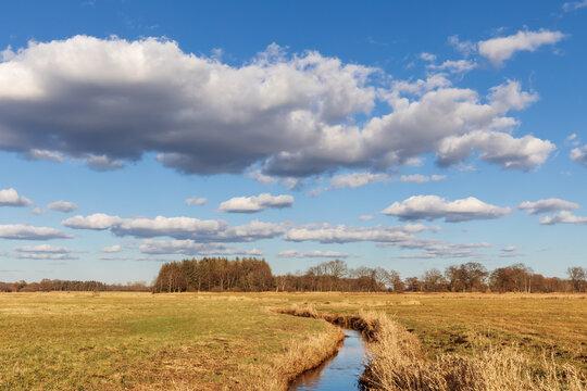 Blauer Himmel mit Wolken über der Oberalsterniederung mit Wiesen und der Alster Anfang März bei Tangstedt in Schleswig-Holstein, Deutschland.