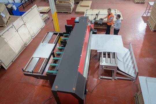 Workers printing cardboard boxes in cardboard box factory