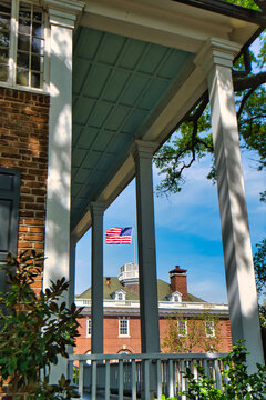 An American flag waving in the wind over a building in Georgetown, South Carolina, USA as seen looking through the porch of an old home.