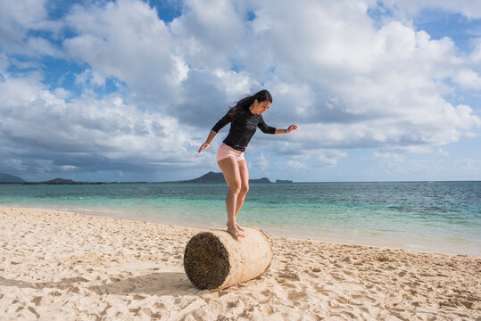 Woman balancing on grass roll, Lanikai Beach, Oahu, Hawaii