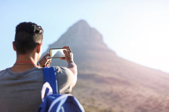Young male hiker photographing mountain in Table Mountain National Park, rear view, Cape Town, Western Cape, South Africa