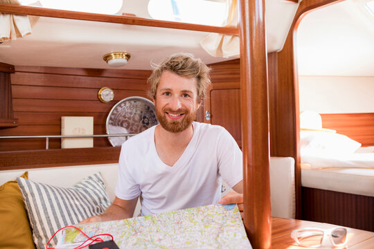 Young man in sailboat cabin with folding map