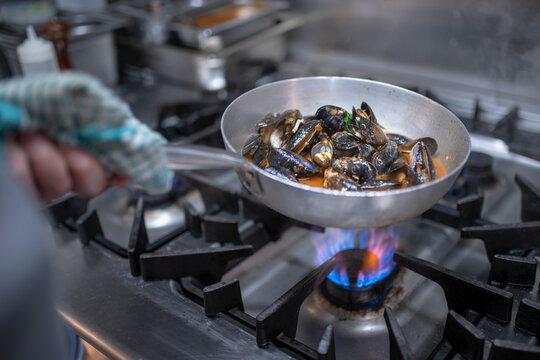 Chef cooking mussels dish on stove in Italian restaurant kitchen