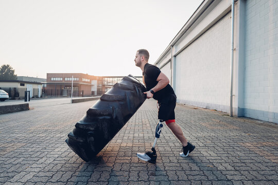 Man with prosthetic leg weight training with giant tyre
