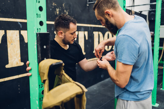 Personal trainer helping man in gym
