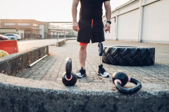 Man with prosthetic leg beside training tyre and kettlebells