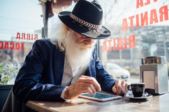 Senior businessman using digital tablet in cafe, Milano, Lombardia, Italy