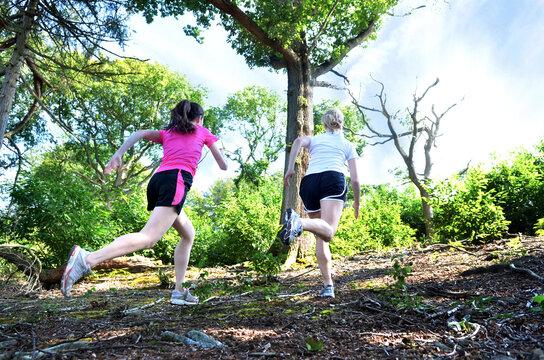 Girlfriends running in forest, Tunbridge Wells, Kent, United Kingdom
