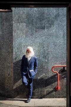 Senior businessman leaning against building wall