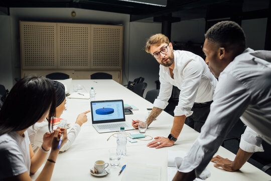 Businessmen and women having discussion over conference table meeting