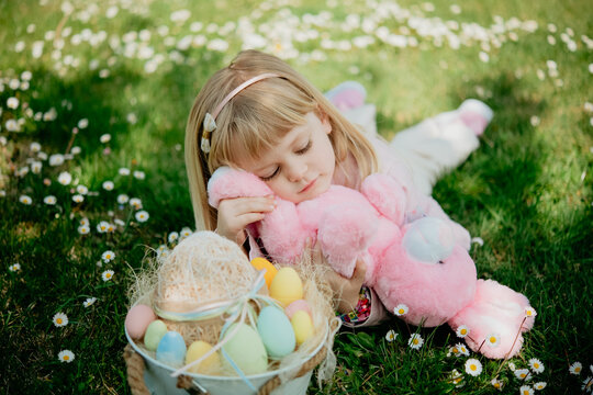 Cute girl lying on grass with toy rabbit and easter egg basket