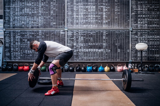 Young man placing weight plate into bar in gym