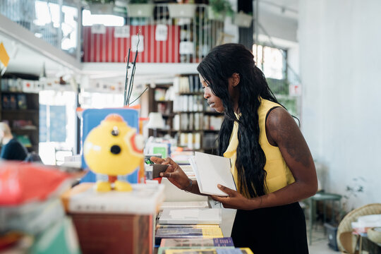 Young businesswoman looking at books in book shop