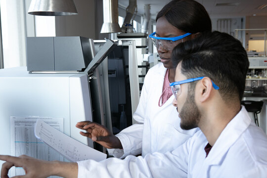Young female and male scientists discussing paperwork in laboratory