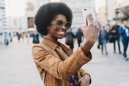 Young woman with afro hair taking selfie in city
