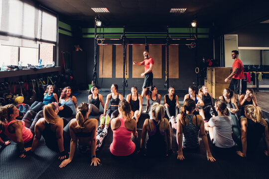 Large group of women training in gym with male trainers, sitting on floor