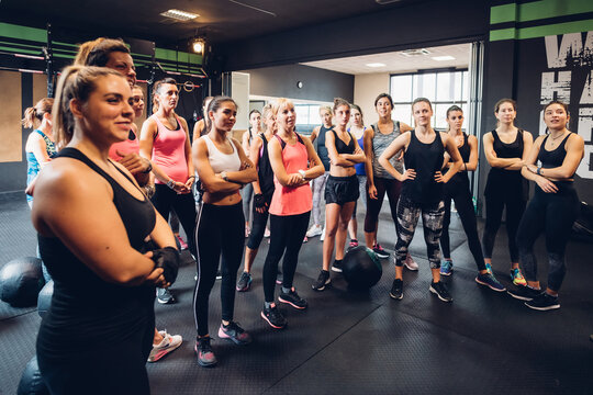 Large group of women training in gym, listening