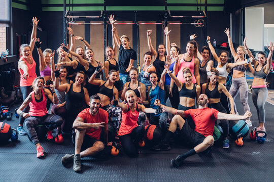 Large group of women training in gym with male trainers, posing for portrait